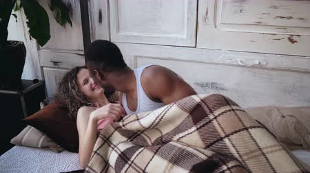 genç çift : Happy young multiethnic couple lying under blanket, hugging and kissing. Tenderly morning of man and woman on the bed.