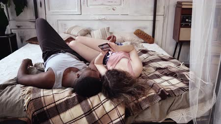 пижама : Young multiracial couple in pajamas lying on the bed and looking photos. Man and woman use smartphone with touchscreen. Стоковые видеозаписи