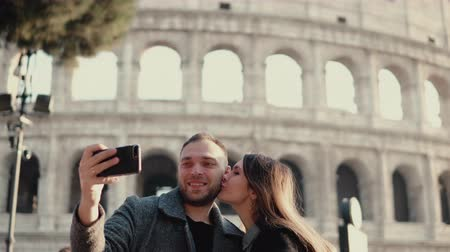 Колизей : Young attractive woman and man standing near the Colosseum in Rome, Italy. Couple takes the selfie photo on smartphone.