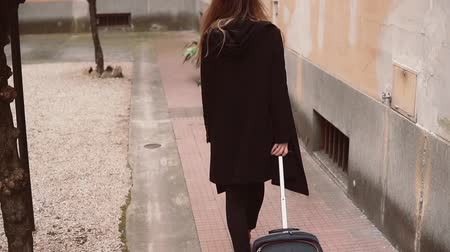 bagagem : Back view of tourist woman in black. Close-up view of female legs walking with a suitcase in the street.