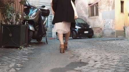 paving : Close-up view of young stylish woman walking on cobblestone pavement road. Girl going through the street. Slow motion.