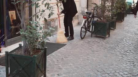 keeper : The man the janitor cleans street. Owners of shop prepares for opening, works with broom. Slow motion.