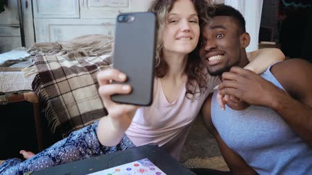 пижама : Beautiful multiethnic couple take the selfie photo on smartphone. Woman hold the smartphone, man kisses her and laughs.