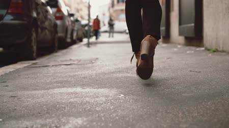 paving blocks : Close-up view of stylish woman walking in little street. Girl wearing shoes on heels goes through the city. Slow motion. Stock Footage