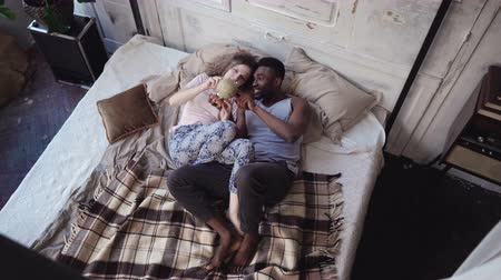 межрасовый : Happy multiethnic couple looking at globe and picking travel destination. Man and woman in pajamas lying on the bed.