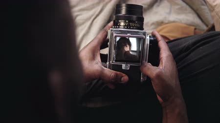 gravador : Close-up view of man opens a video recorder cover of old moving-fil camera. Photographer takes the photo of young woman.
