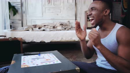 resistência : African handsome man in pajamas throws the dice and laughs. Multiethnic couple playing the board game on the floor. Vídeos
