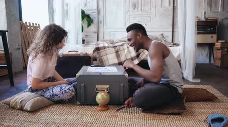 ırklararası : Multiracial couple in pajamas sitting on the floor and playing the boar game. Woman throws the dice, man waits his turn. Stok Video