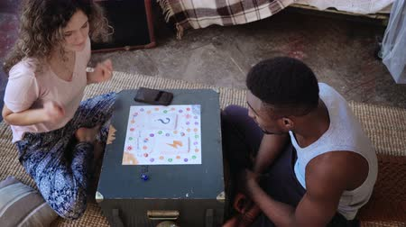 kości do gry : Multiracial couple, man and woman in pajamas playing the board game. Girl throws dice and dancing, moves on the field.