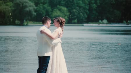 жених : Wedding day. Beautiful couple enjoy their happiness standing on a quay, hugging and kissing. Wedding outfit, bouquet