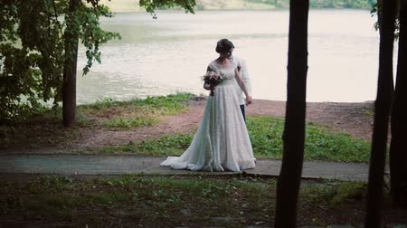 cultura juvenil : Couple in love on a river bank on their wedding day. Happy bride turns and shows her beautiful dress to her groom