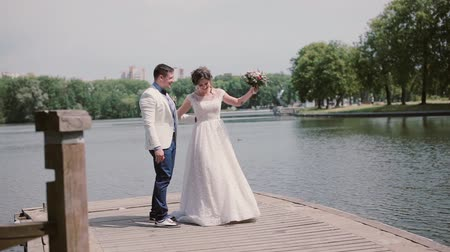 atender : Happy couple on their wedding day dancing and having fun on a quay. River in a park in summertime. Wedding outfits Stock Footage