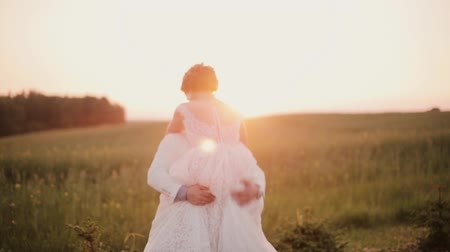жених : Happy bride jumps into her grooms arms, he catches her and swirls around in a field at sunset. Wedding on a summer day. Стоковые видеозаписи