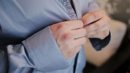 mandzsetta : Close-up view of male hands buttons a striped shirt. Morning of the groom preparing for a wedding, putting his suit on. Stock mozgókép