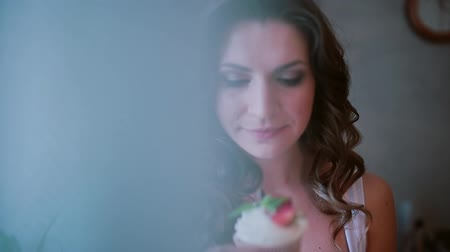 cortinas : Portrait of young beautiful woman standing near the window. Girl smells the cupcake. View through the curtain.