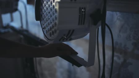 lights up : Close-up view of male hands fixing the lighting equipment on the construction. Man holds stage light projector. Stock Footage
