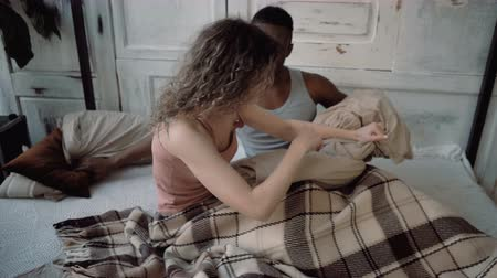 almofada : Multiracial couple spending time together. Male and female lying on bed, laughing. Man and woman fighting with pillows. Vídeos