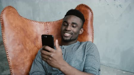 cultura juvenil : Portrait of African man sitting in the chair and using the Smartphone. Male is surfing the internet, smiling. Stock Footage