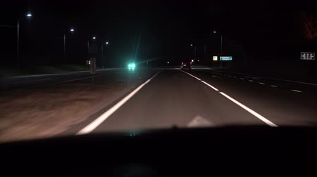 hız göstergesi : Night road view from inside a car. The headlight and other car in motions on the country road. Stok Video
