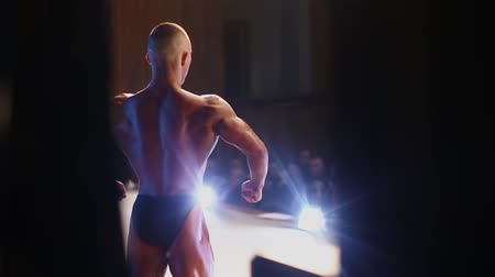 categoria : Bodybuilding competitions. Bodybuilder posing in front of audience. Backview of a man demonstrating muscles