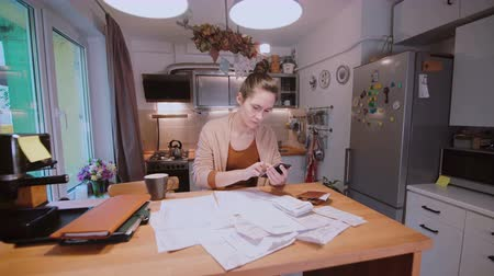 bankjegyek : Young woman sitting at the table in kitchen and calculating bills. Home accounts department. Checking the bills. Stock mozgókép