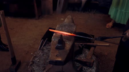 ручная работа : Close-up view of blacksmith working with hammer and hot red metal. Man forge the iron on the anvil in smithy.