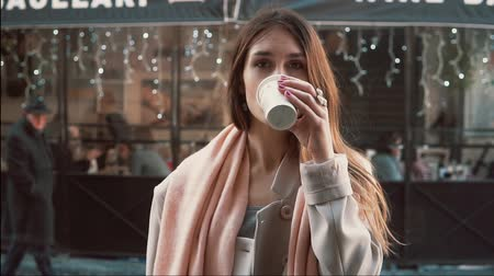 doubt : Young brunette woman with cup of coffee standing in front of show-window. Girl dreaming to buys clothes. Slow motion. Stock Footage