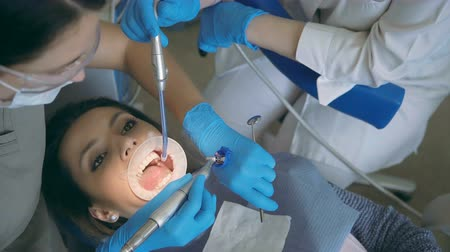 scrutiny : Dentist with dental nurse treating the patient teeth. Woman visiting the dental clinic, checking-up her mouth. Stock Footage