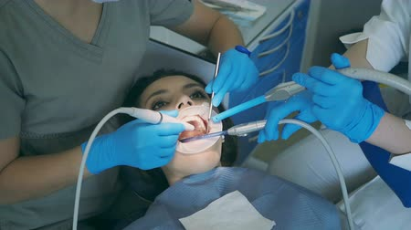 autêntico : Young woman sitting in the dental chair with opening wide mouth. Dentist with nurse clean and polish teeth.