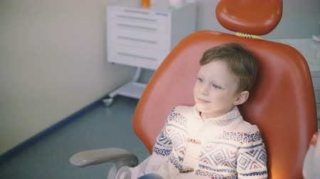 scrutiny : Cute little boy before the doctor reception. Girl kisses brother, sister supports him. Male sitting in dentist chair. Stock Footage
