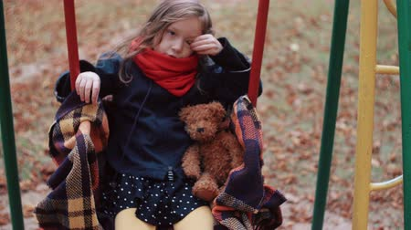 miserável : cute little girl on a old swing with her teddy bear in autumn park 4k Stock Footage