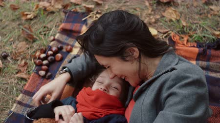 плюшевый мишка : mother with her cute little daughter lying on the plaid Mom tickling and kisses girl in the nose in autumn park 4k