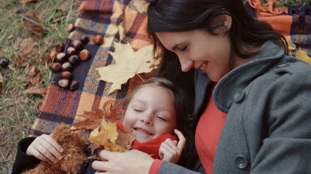 плюшевый мишка : beautiful mother with her cute little daughter lying on the plaid playing with maple leaves in autumn park 4k Стоковые видеозаписи