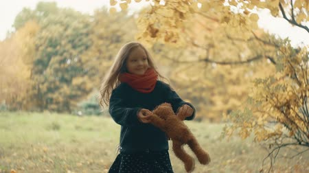 плюшевый мишка : funny, cheerful cute little girl spinning with her toy, teddy bear yellow in the amazing autumn park slow motion