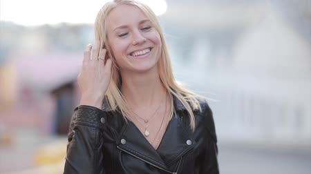seriously : Young blonde woman standing in the street and looking at camera. Girl seriously looks and then starts to smile.