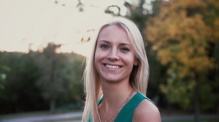 camera rotation : Portrait of young blonde woman standing in the park on sunset and looking at camera. Happy girl spending time outside. Stock Footage