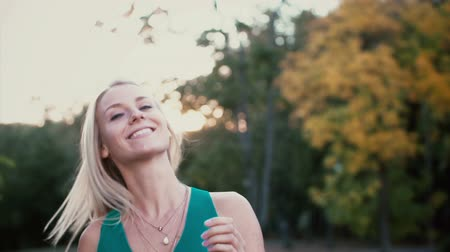 camera rotation : Young woman standing in the park on sunset, looking at camera. Girl seriously looks and then starts smile, hair waving. Stock Footage