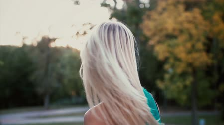 camera rotation : Back view of young blonde woman in park on sunset. Girl moving her head and hair waving on the wind. Slow motion.