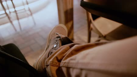 süet : Crossed male legs with brown jeans and boots on under the table in a bar Stok Video