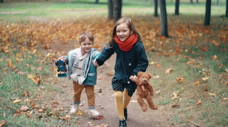 приехать : cute brother and sister little boy and girl running holding hands, with their toys through autumn alley in park slow mo