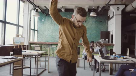 kutluyor : Handsome young businessman doing victory dance about successful achievement. Happy male at modern trendy office.