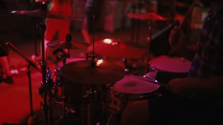 estréia : Close-up view of drummer plays on stage. Concert rock band in a nightclub or prom. Man uses a musical instrument.