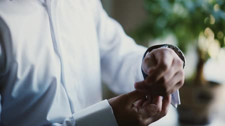 punctuality : Man in a white shirt puts on a watch. Young businessman getting ready at the morning. Close-up view of male hands. Stock Footage