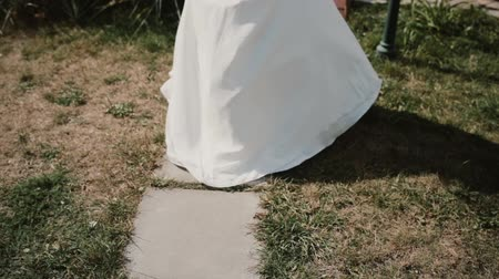 lem : Close-up view of young woman in white dress running at park. Female changes her mind about wedding ceremony.