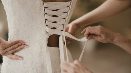 затянуть : Close-up view of female hand helping bride to puts on dress. Bridesmaid lacing wedding dress on the back before ceremony