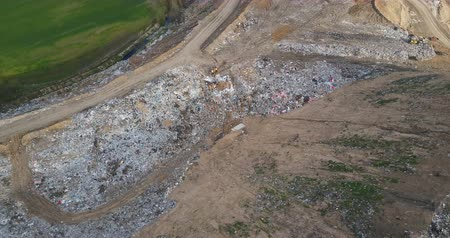 decomposition : Aerial view of the urban dump. Drone flight over the big piles of garbage trash and excavator.