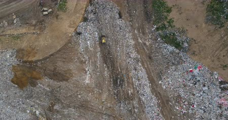 spotřebitel : Copter turning over the urban dump. Aerial view of the pile of trash and sanitation vehicle, working car. Dostupné videozáznamy