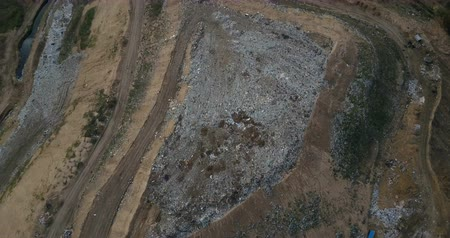 rendetlenség : Aerial drone shot of the garbage disposal site. Flight over the urban refuse dump. Big piles of trash. Stock mozgókép