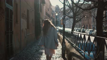 vintage car : Back view of young woman with long hair walking in the street at bright sunny day. Female tourist exploring the new city