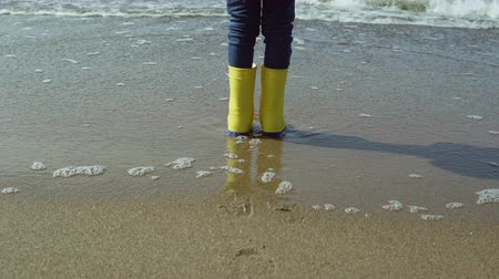 legs only : Close-up view of little girl foot in bright yellow rubber boots. Child standing on shore of beach, footprints in sand. Stock Footage